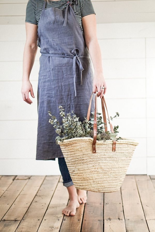 styled photography of a linen apron and French Market basket with eucalyptus