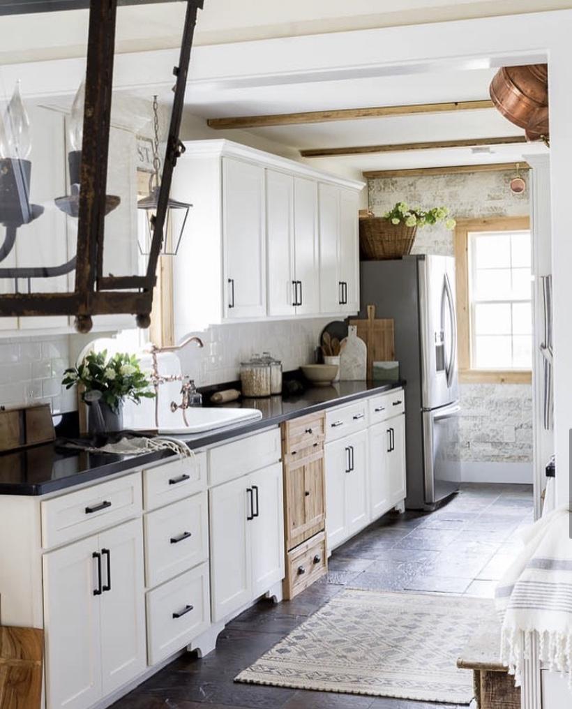 english cottage kitchen hidden dishwasher white cabinets dark counter top