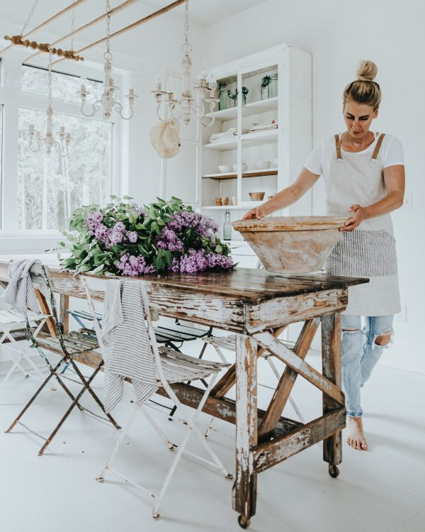 Britt's vintage farmhouse dining table britt holding tein pot with lilacs laid on the table