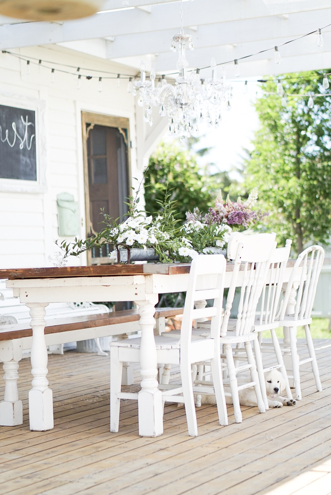 spool leg farmhouse dining table on the patio with mix match vintage chairs